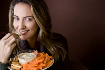 A mid adult woman eating crudites and dips