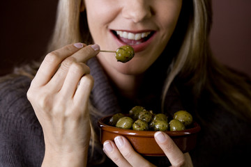 A mid adult woman eating an olive