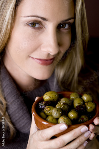 A mid adult woman holding a dish of mixed olives