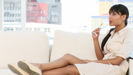 Relaxed businesswoman drinking Champagne sitting on a sofa