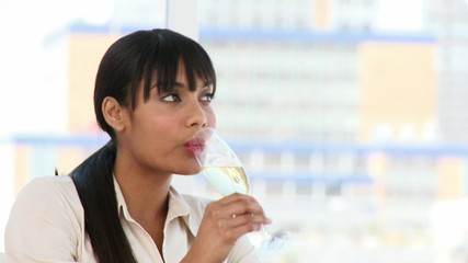 Portrait of an ethnic woman drinking champagne