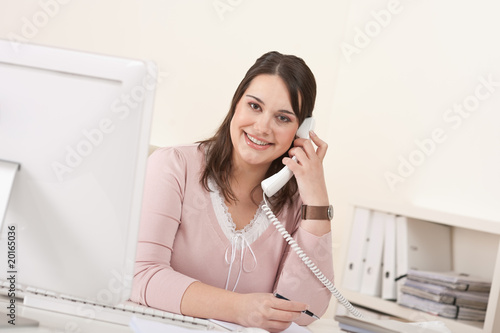 Young secretary on phone at modern office