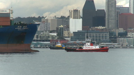 Cargo ship being guided by tug boat near seattle