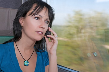 beautiful young worried woman  in a train making a phone cal