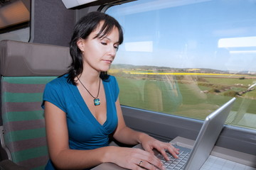 beautiful young woman woman in a train using a computer lap to