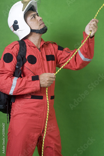 man firefighter pulling a rope isolated on green