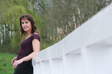 Frau Mitte 40 lehnt an weißem Geländer