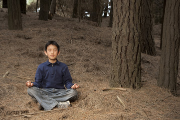 Asian boy meditating in pine forest
