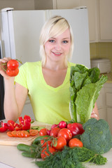 Young blond woman with vegetables on kitchen