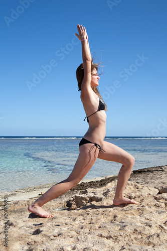 girl  practicing yoga at sea coast