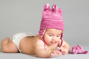 Laying baby in stripy pink cap