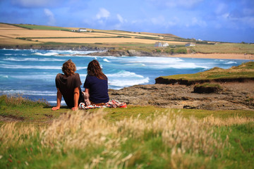 A couple sitting overlooking a beach in England