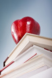 Education metaphor with red apple and books poster