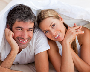 Enamoured couple having fun lying on a bed