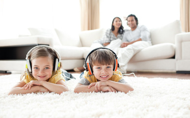 Cute siblings listening music with headphones