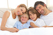 Happy family reading a book on bed