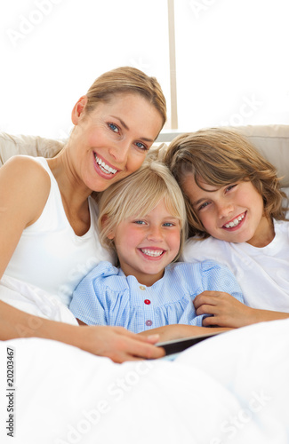 Attractive mother and her children reading book