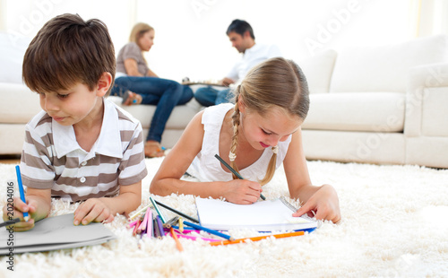 Cute siblings drawing lying on the floor