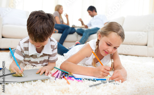 Concentrated siblings drawing lying on the floor