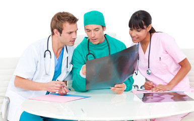 Concentrated medical team looking at X-ray
