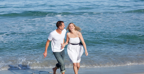 Happy lovers having fun at the seaside