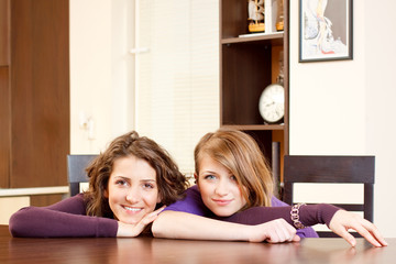 portrait of two girls sitting on a kitchen table