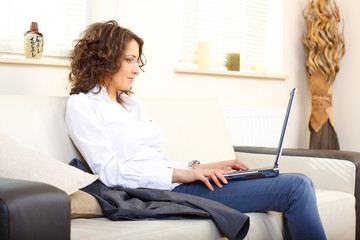 businesswoman on a couch using a laptop