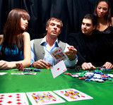 Stylish man in black suit folds two cards in casino
