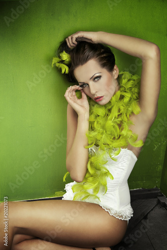 Portrait of a young brunette beauty over green wall