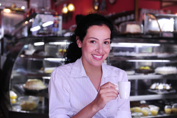 woman drinking a coffee at a pastry shop