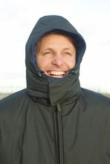 happy smiling outdoor man wearing a hoodedwinter  coat