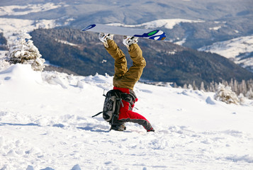 Snowboarder standing on a head in snow