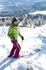Female skier standing on the hill