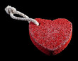 red heart-shaped stone with rope isolated on black