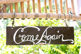 come again phrase on wooden board poster