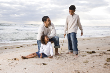 African-American father and children playing together on beach