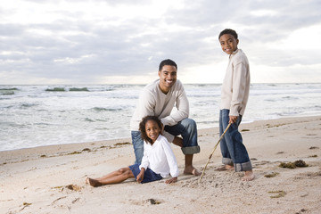Happy African-American father and two children together on beach