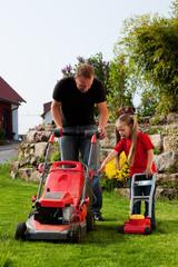 Vater und Kind mähen zusammen den Rasen