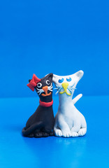 Two funny friendly clay black and white cats with copyspace