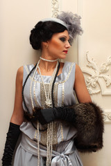 Beautiful girl in furs and pearls on the background of the palac