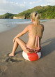 bikini woman sitting on colorful beach ball on tropical costa ri