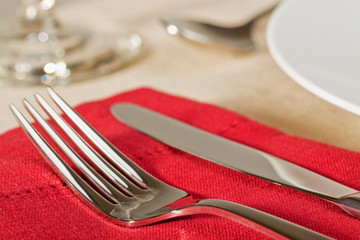 Elegant placesetting of knife and fork on red