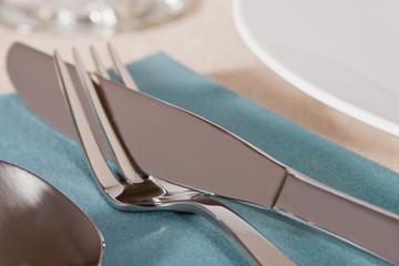 Elegant placesetting of knife and fork on blue