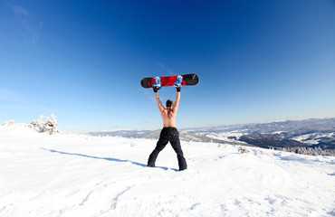 Snowboarder topless standing on the mountain