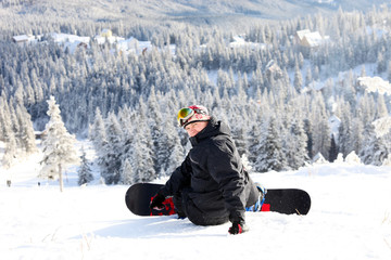 Sitting snowboarder on slope - winter sport scene