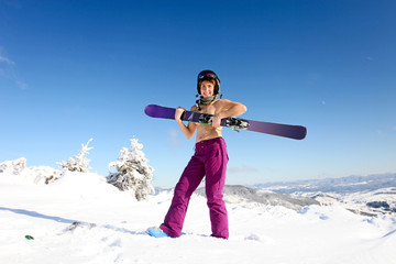 Female skier topless with a ski standing on the heel