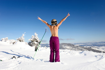 Female skier topless with a ski standing on the heel a back
