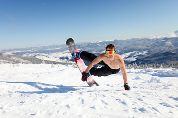 Snowboarder jumps up on the mountain slope