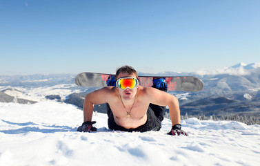 Snowboarder topless on the mountain slope
