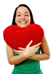 Woman cuddling heart shaped pillow